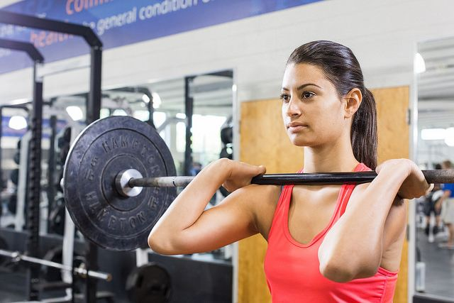 Woman in red tank lifting weights