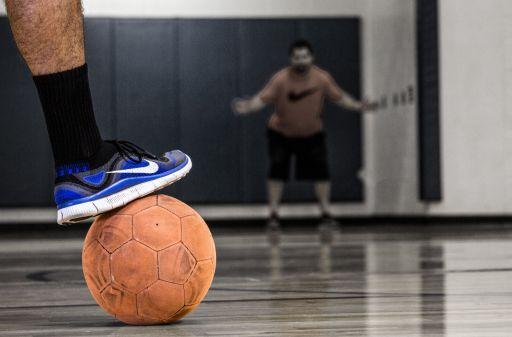 Basketball player stepping on a ball